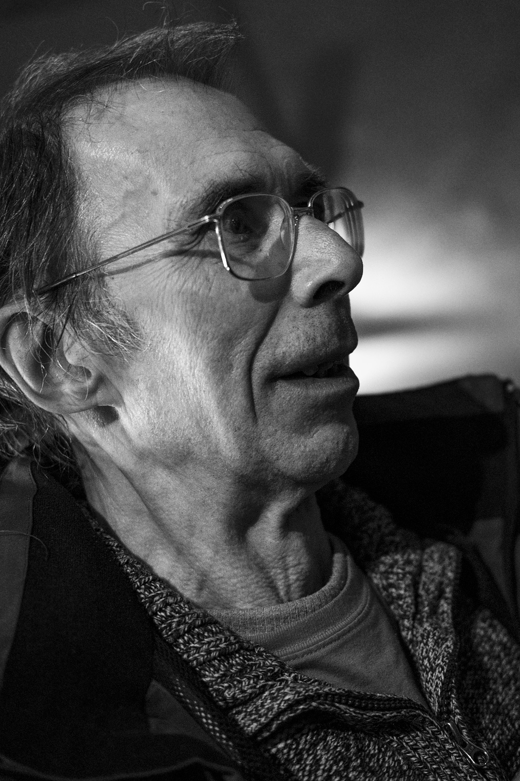 Man wearing spectacles looking sideways in conversation candid black and white portrait Brighton UK © P. Maton 2018 eyeteeth.net