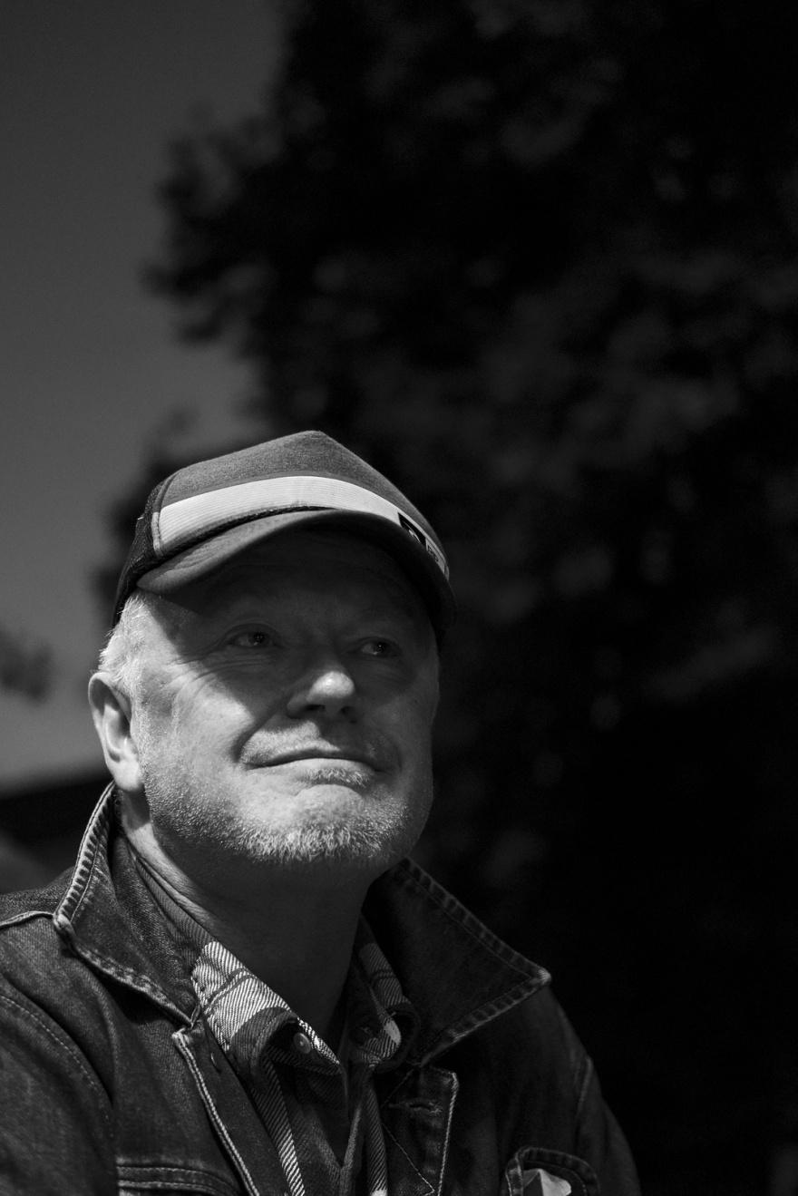 Senior man wearing baseball cap and denim jacket with check shirt, Brighton UK monochrome black and white documentary portrait ©P. Maton 2018 eyeteeth.net