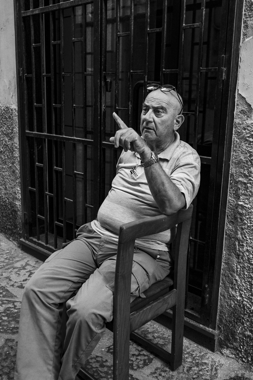 Seated man pointing via dellindipendenza Gaeta Italy black and white monochrome candid street portrait photography ©P. Maton 2018 eyeteeth.net
