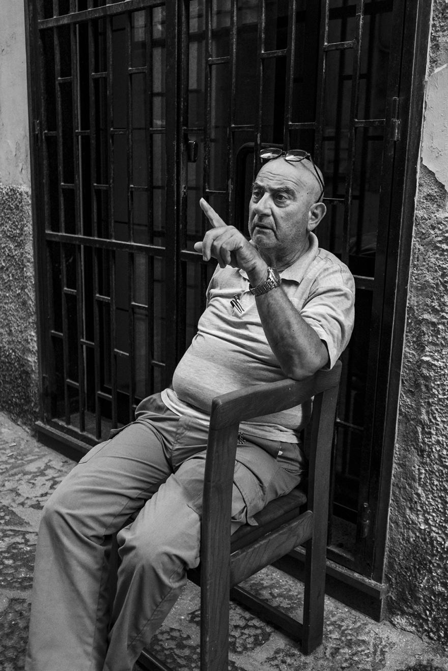 Seated man pointing via dellindipendenza Gaeta Italy black and white monochrome candid street portrait photography ©P. Maton 2018 eyeteeth.net