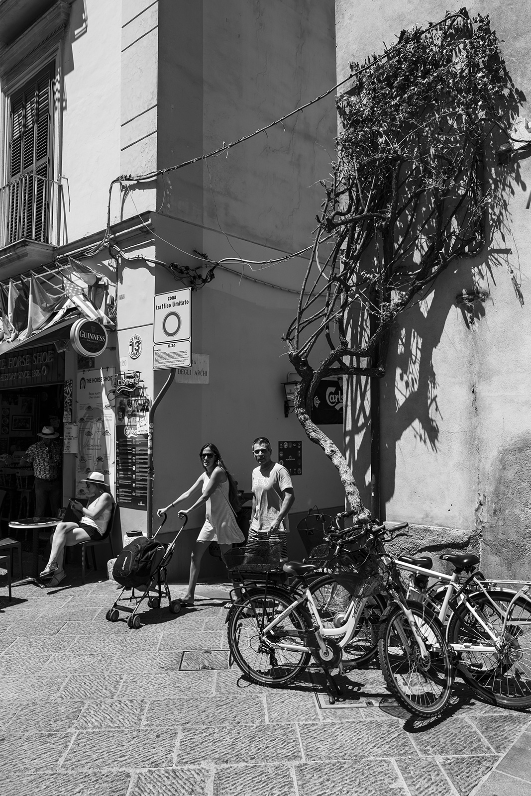 couple with pram walking by pushbikes and the horse shoe on corner of corso italia and via degli archi sorrento Italy, black and white street scene monochrome portrait © P. Maton 2018 eyeteeth.net