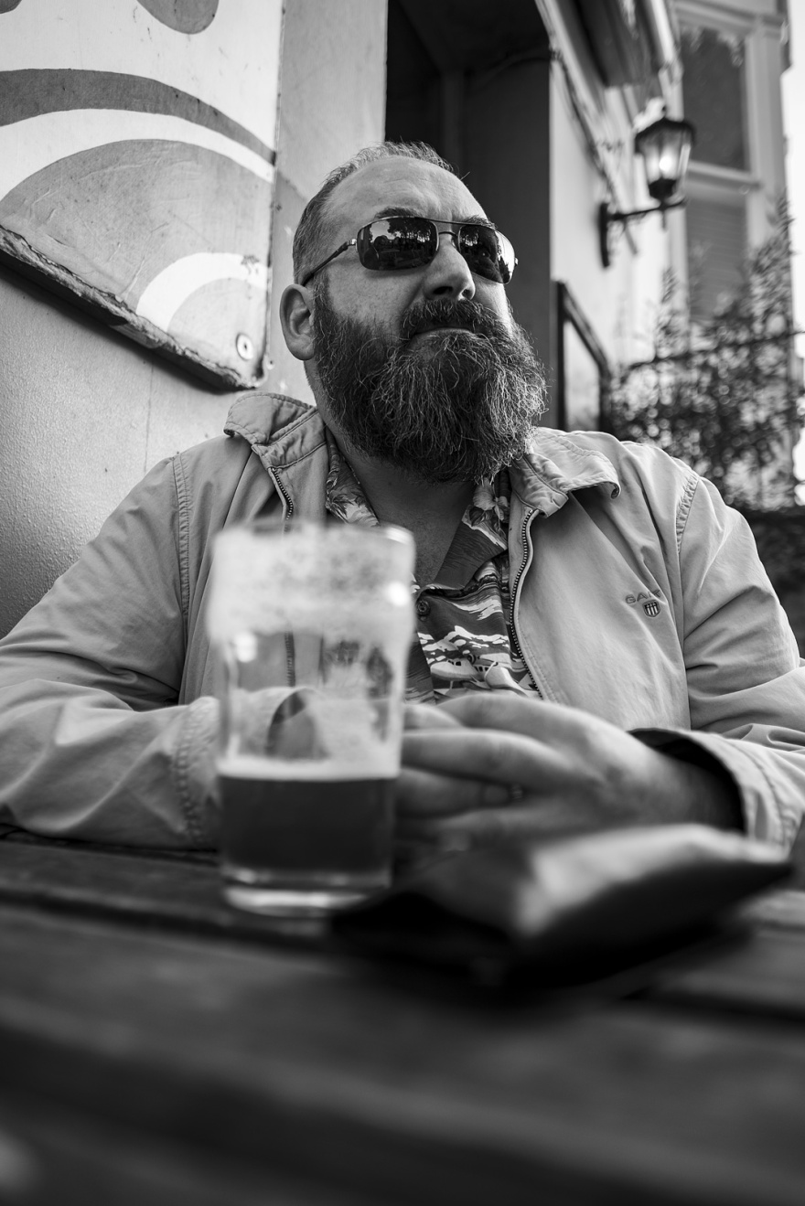 Man with beard wearing wearing dark glasses with pint of beer and tobacco pouch candid black and white portrait Brighton UK © P. Maton 2018 eyeteeth.net