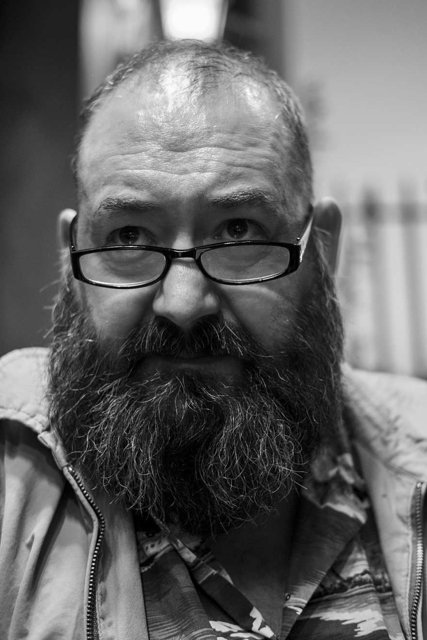 Man looking over spectacles with full beard and and thinning hair candid black and white portrait Brighton UK © P. Maton 2018 eyeteeth.net