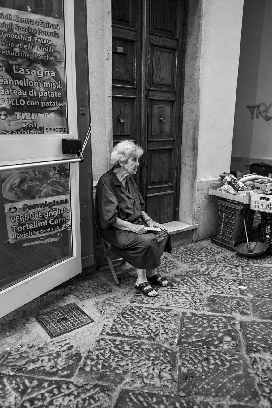 elderly woman holding envelope sitting on chair in street with flag stone floor Via dell'indipendenza Gaeta Italy black and white monochrome street documentary portrait ©P. Maton 2018 eyeteeth.net