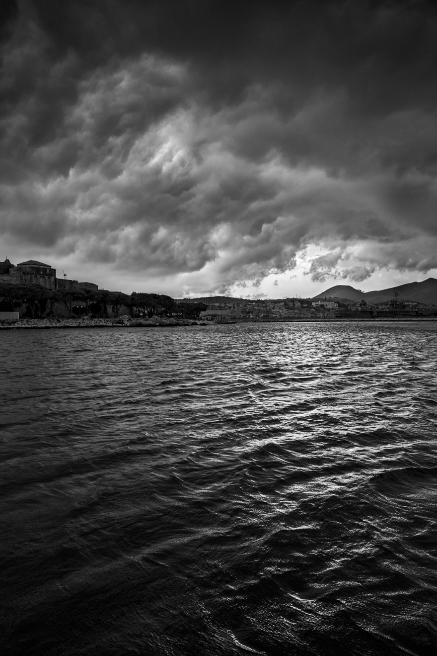 Dramatic thunder storm clouds gathering over port of Gaeta Italy viewed from the sea, black and white vertical landscape ©P. Maton 2018 eyeteeth.net
