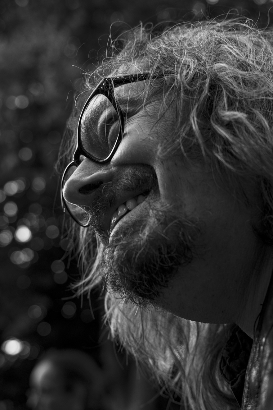 Smiling man with spectacles, beard and long hair candid black and white portrait Brighton UK © P. Maton 2018 eyeteeth.net