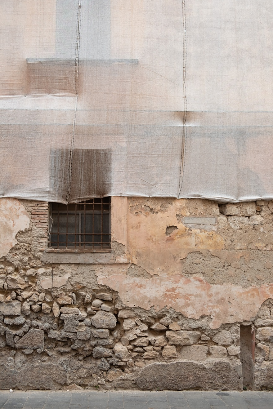 Windows in stone wall with crumbling render partially covered by cloth screening Via Annunziata Gaeta Italy abstract colour portrait composition urban street rustic photograph © P. Maton 2018 eyeteeth.net
