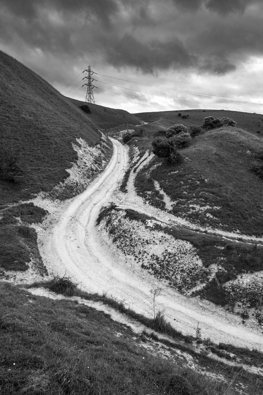 Chalk Droveway road leading up hill with electricity pylon on horizon Edburton Escarpment West Sussex UK Black and white portrait rural landscape photography ©P. Maton 2018 eyeteeth.net