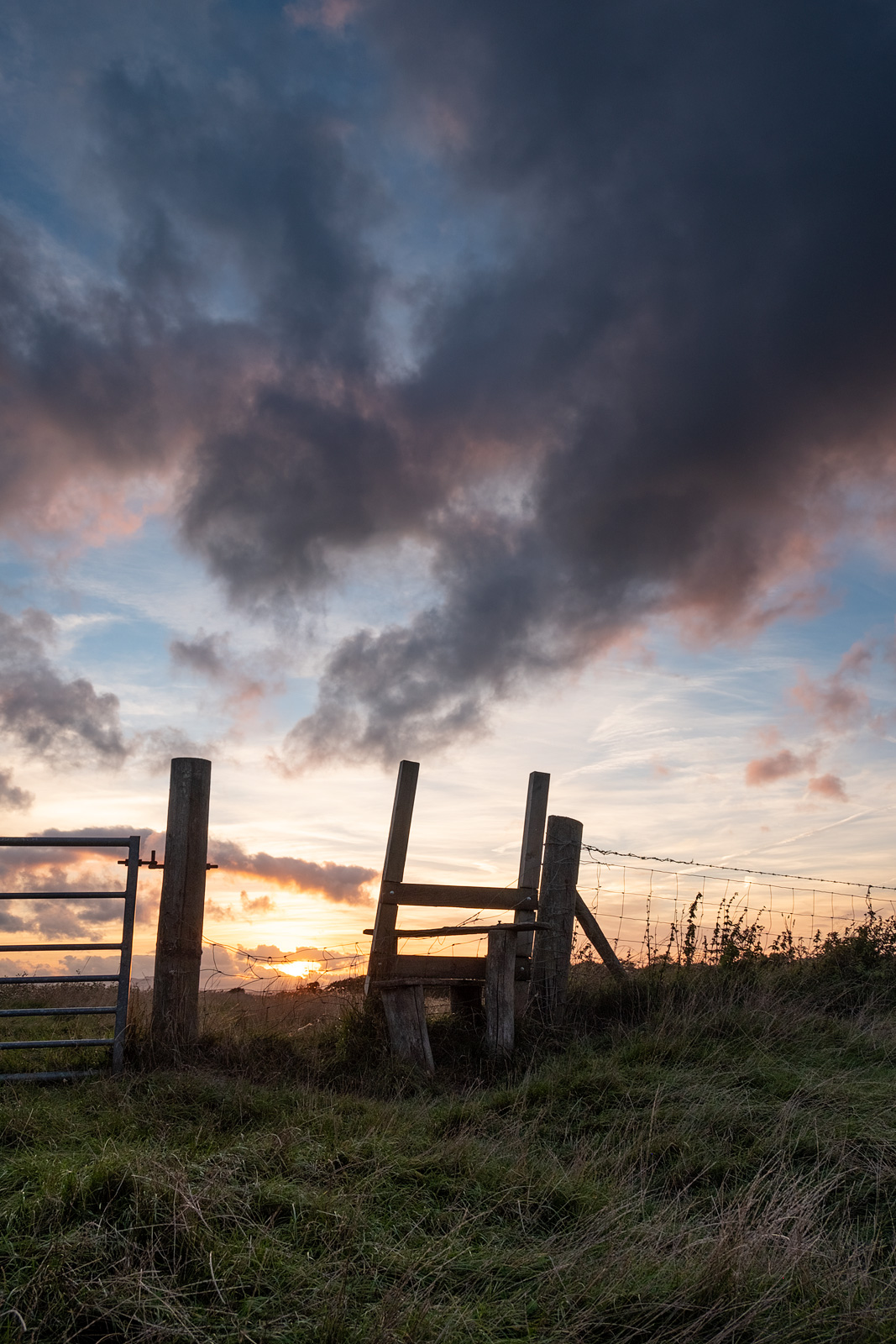 Sunset with crooked stile and farm gate in foreground with dramatic colourful clouds Mill Lane Poynings West Sussex UK colour nature photograph portrait ©P. Maton 2018 eyeteeth.net