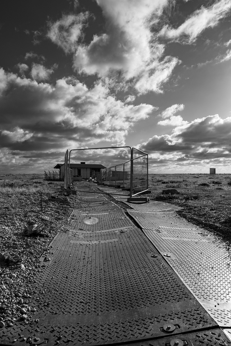 New building construction site, rubber path over shingle with site fencing and dramatic clouds in sky, Dungeness Kent UK, black and white monochrome landscape portrait © P. Maton 2018 eyeteeth.net