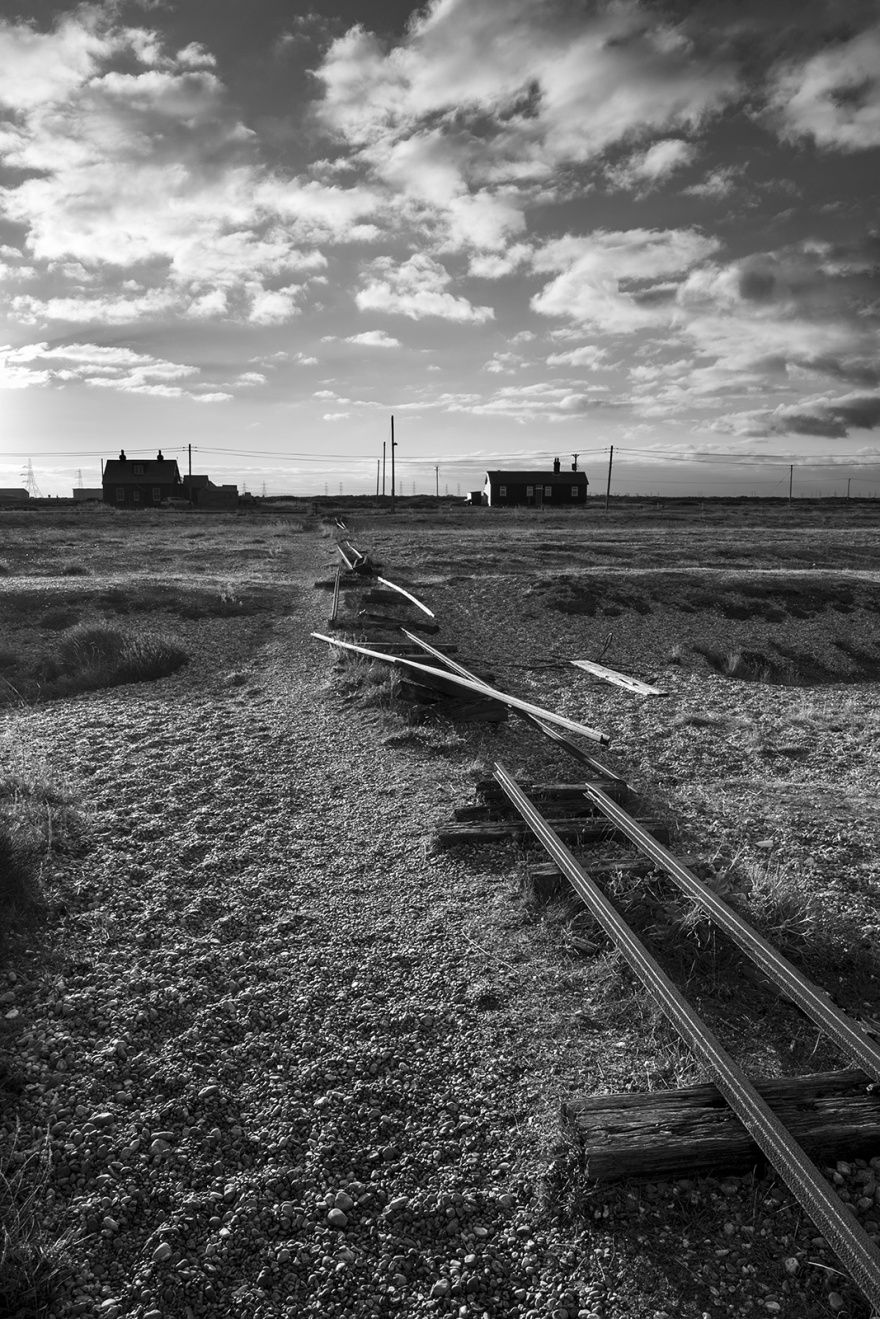 Buckled rusty disused narrow gage railway tracks on shingle beech with small houses in background and dramatic clouds in sky, Dungeness Kent UK, black and white monochrome landscape portrait © P. Maton 2018 eyeteeth.net