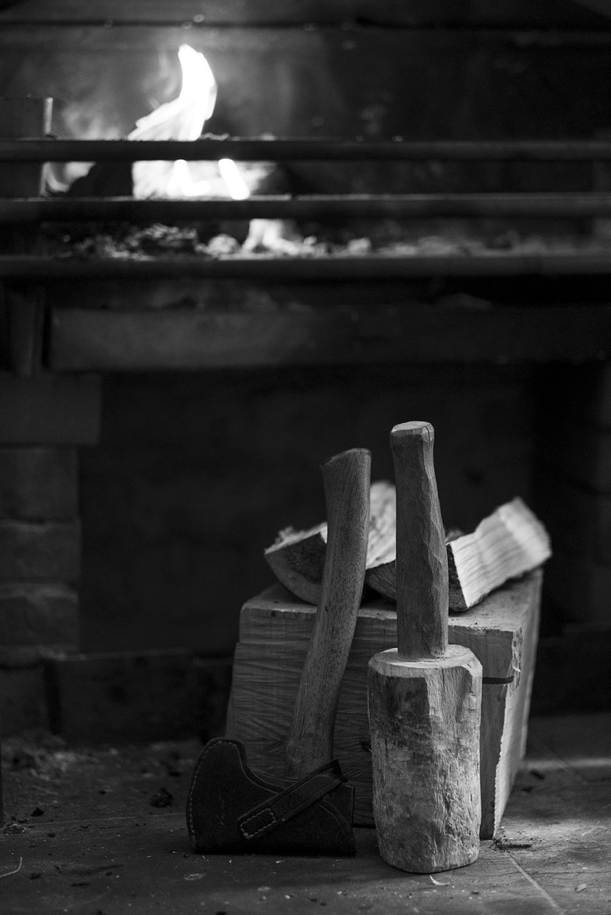 Hatchet axe and maul mallet with split wood on block with fireplace in background, black and white rural lifestyle photograph © P. Maton 2018 eyeteeth.net