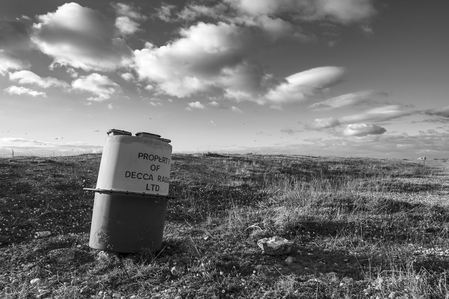 abandoned Decca radar buoy on beach with dead grass and dramatic clouds in sky, Dungeness Kent UK, black and white monochrome landscape portrait © P. Maton 2018 eyeteeth.net