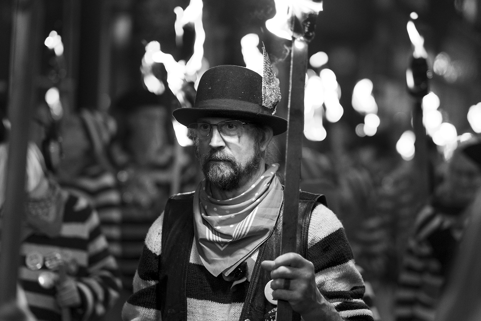 Male torch bearer in bowler hat and spectacles Lewes bonfire night Cliffe High Street Lewes East Sussex UK, black and white night photography Britain © P. Maton 2018 eyeteeth.net