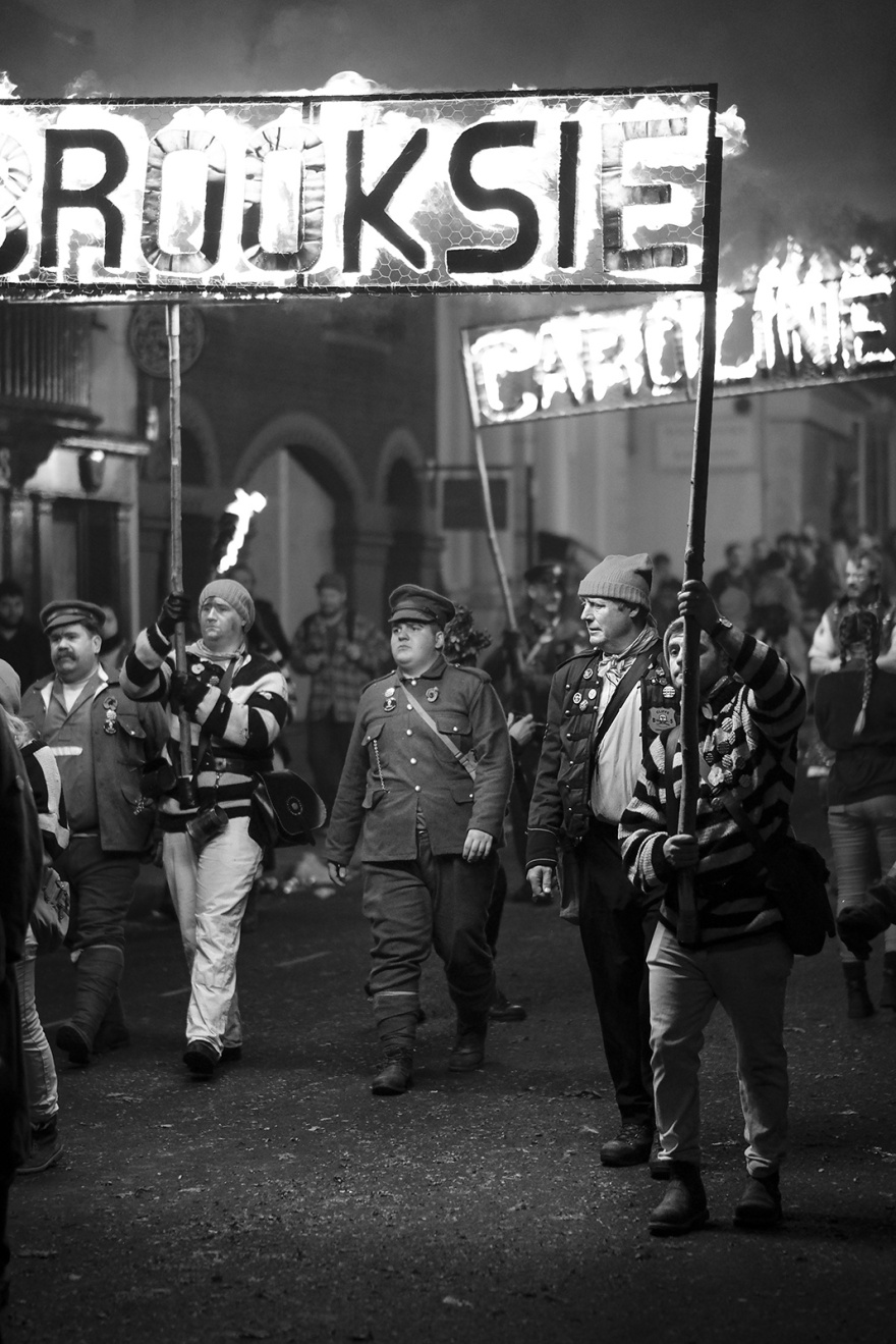 Male torch bearers in costume with burning standards Lewes bonfire night High Street Lewes East Sussex UK, black and white night photography Britain © P. Maton 2018 eyeteeth.net