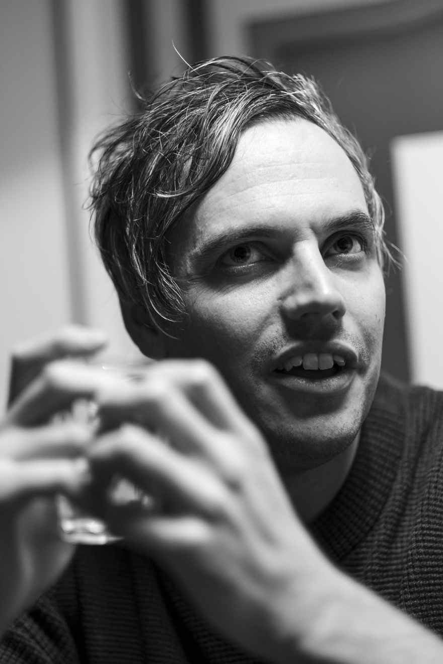 Portrait of man in conversation looking up with whisky glass in his hands, lit from above, black and white portrait documentary britain © P. Maton 2018 eyeteeth.net