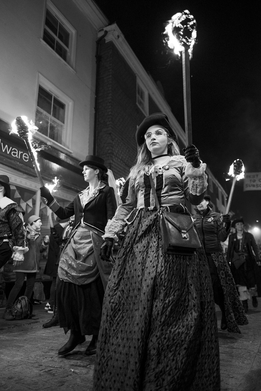 Female torch bearers in period costume with burning torches Lewes bonfire night Cliffe High Street Lewes East Sussex UK, black and white night photography Britain © P. Maton 2018 eyeteeth.net