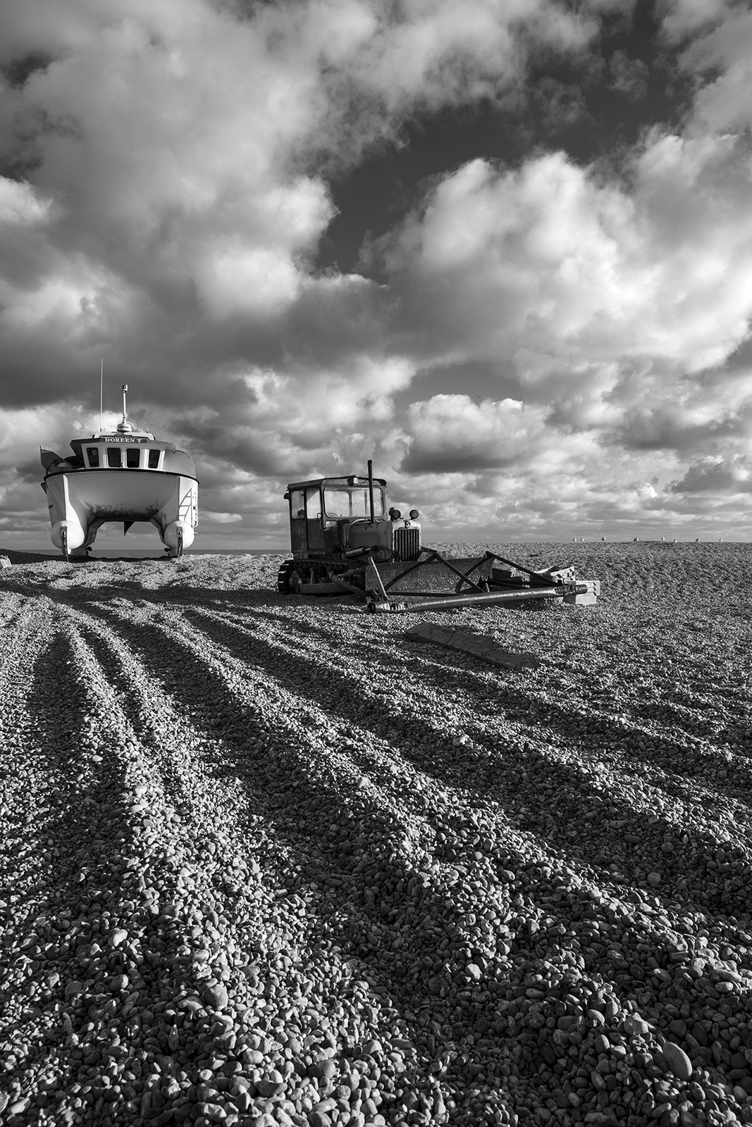 Fishing boat catamaran next to bulldozer on shingle beach with track marks and dramatic clouds in sky, Dungeness Kent UK, black and white monochrome landscape portrait © P. Maton 2018 eyeteeth.net
