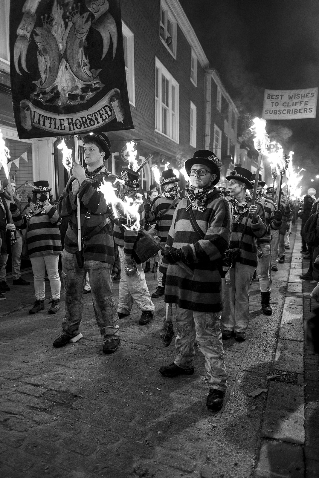 Little Horsted Male torch bearers in striped costume with burning standards Lewes bonfire night Cliffe High Street Lewes East Sussex UK, black and white night photography Britain © P. Maton 2018 eyeteeth.net