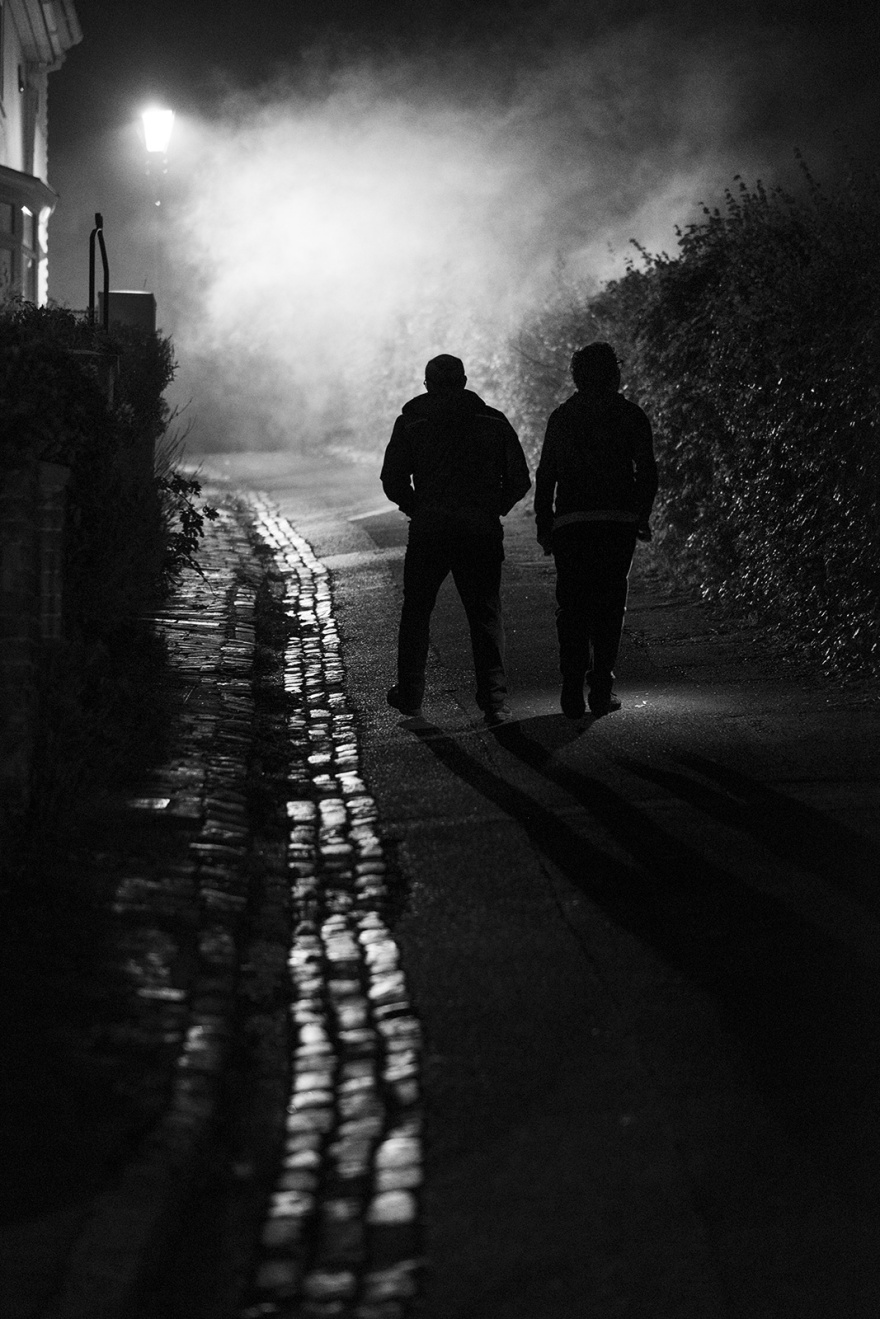 Two silhouetted figures walking up Chapel Hill cobbled street towards street lamp illuminating smoke in distance, Lewes bonfire night Cliffe, black and white night portrait Britain © P. Maton 2018 eyeteeth.net