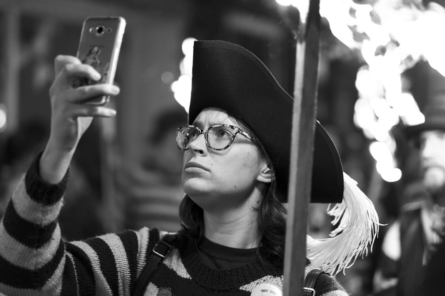 Female torch bearer in striped jersey and tricorn hat with phone and burning torches Lewes bonfire night Cliffe High Street Lewes East Sussex UK, black and white night photography Britain © P. Maton 2018 eyeteeth.net