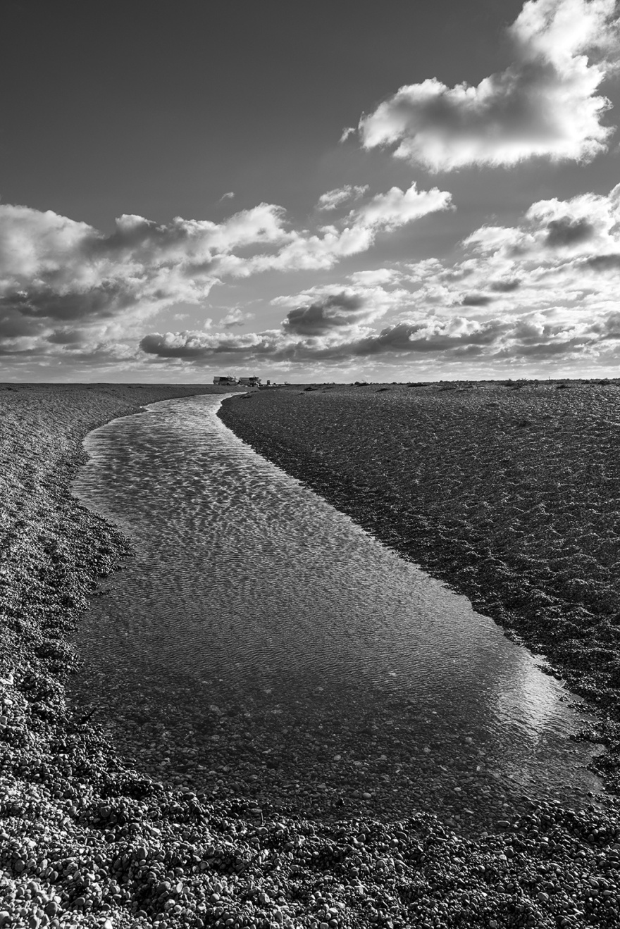 Water channel in shingle beach with texture and dramatic clouds in sky, Dungeness Kent UK, black and white monochrome landscape portrait © P. Maton 2018 eyeteeth.net