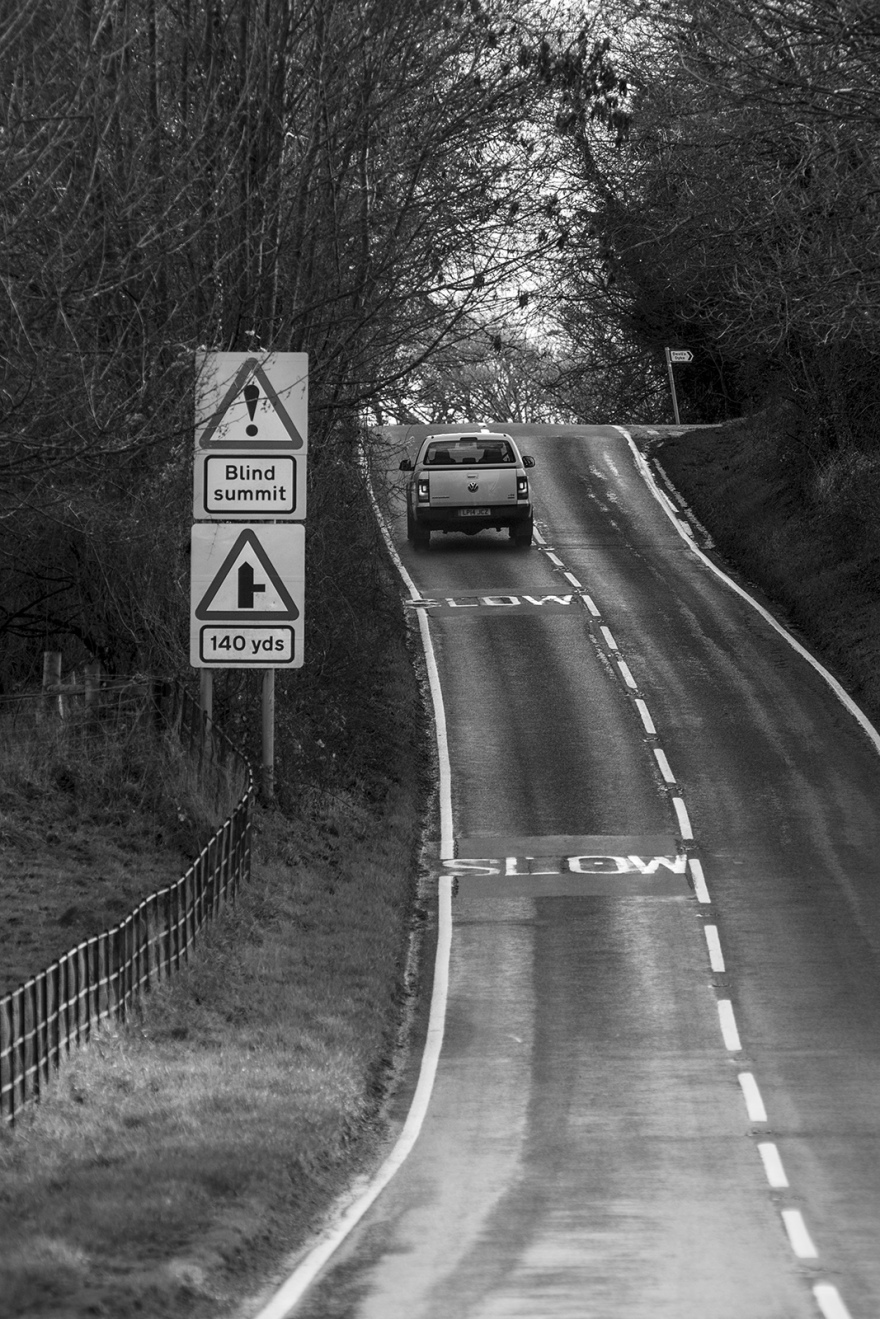 SUV driving up hill on road with slow warnings and warning sign of Blind Summit and junction to Devil's Dyke, Saddlescombe Road West Sussex uk black and white portrait composition rural countryside documentary photograph ©P. Maton 2018 eyeteeth.net