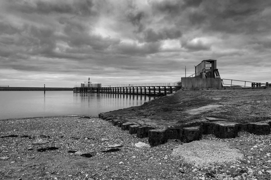 Shoreham harbour central pier with navigation beacon by entrance to eastern arm black and white landscape seascape with structures and overcast sky Shoreham by Sea West Sussex UK ©P. Maton 2019 eyeteeth.net