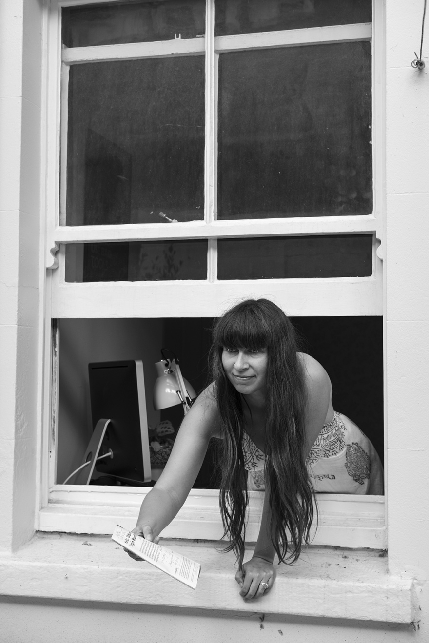Author Eleanor Wood leaning out of a sash window holding a written paper document, black and white portrait documentary photograph Brighton UK  ©P. Maton 2018 eyeteeth.net