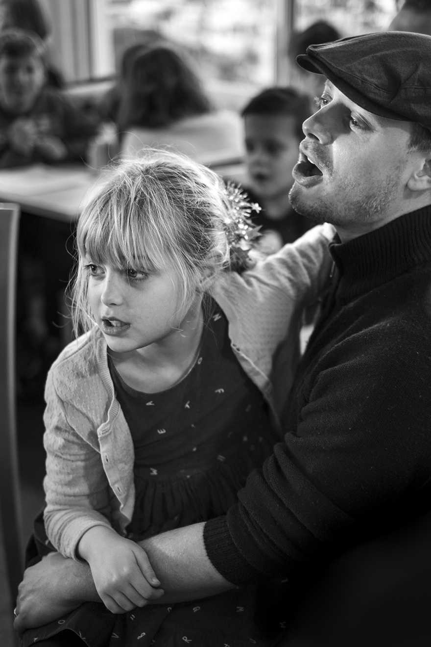 Man singing with daughter on his lap folk and sea shanty songs, The Boathouse in the Marina, Littlehampton West Sussex UK black and white portrait documentary culture folk music ©P. Maton 2018 eyeteeth.net