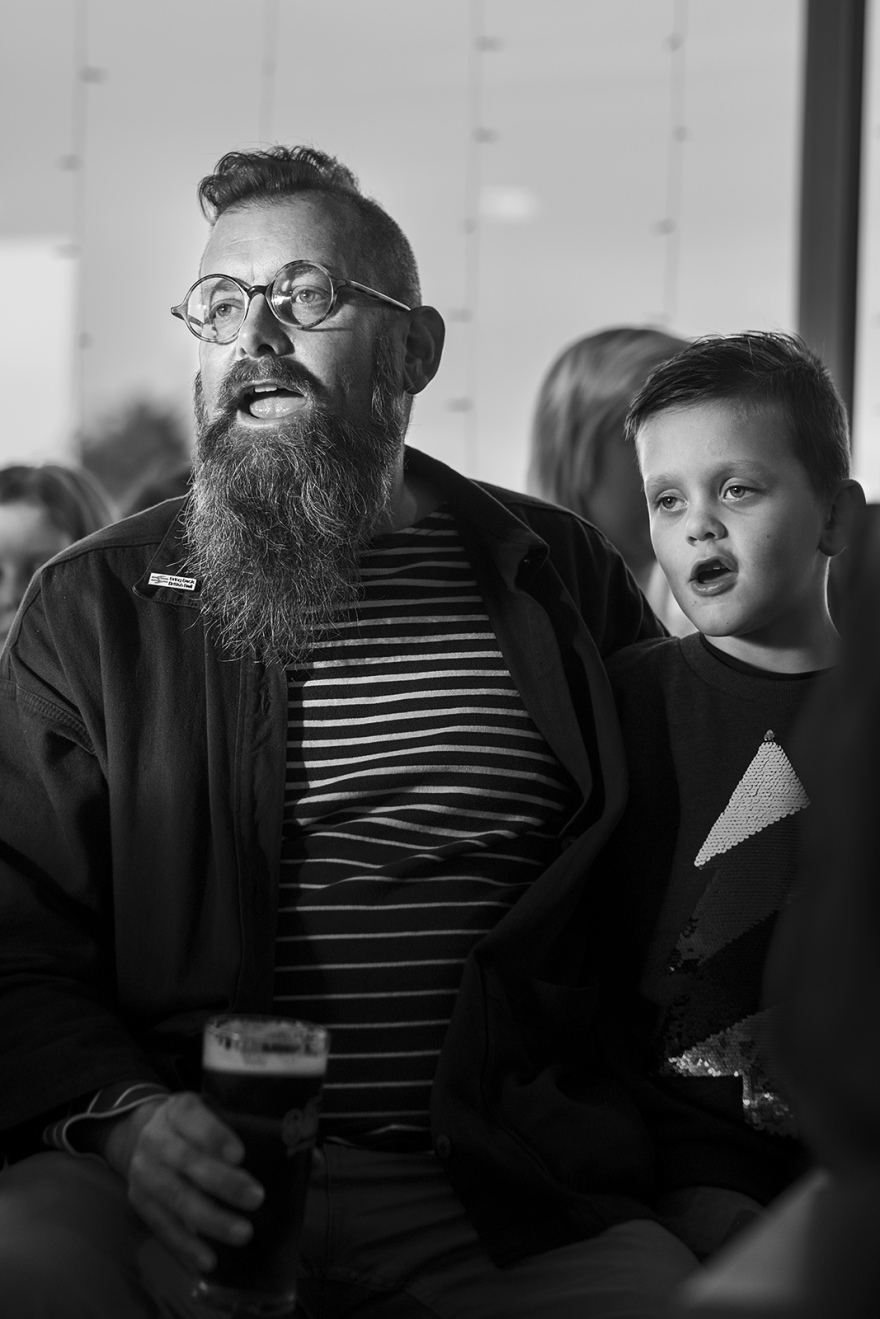 Man singing with son beside him, folk and sea shanty songs, The Boathouse in the Marina, Littlehampton West Sussex UK black and white portrait documentary culture folk music ©P. Maton 2018 eyeteeth.net