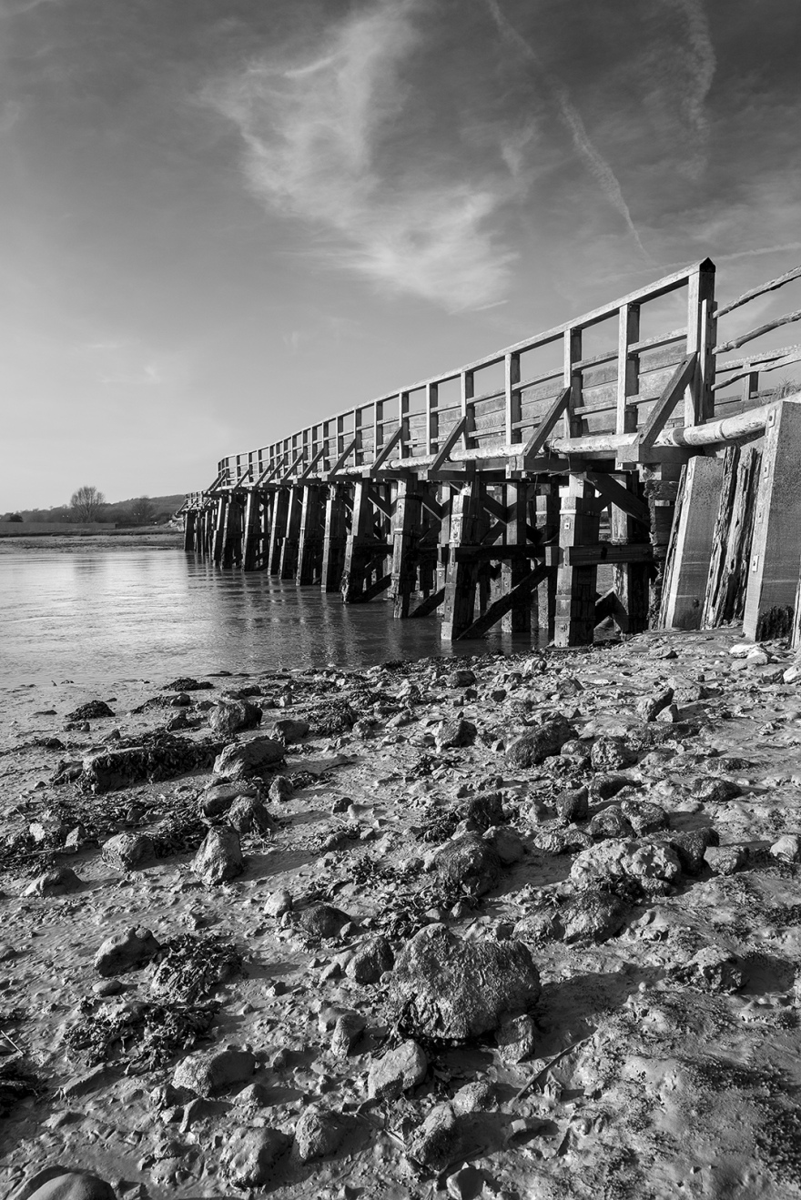 Footbridge spanning the River Adur near Shoreham by Sea West Sussex with mud and rocks in foreground black and white portrait composition rural landscape ©P. Maton 2019 eyeteeth.net