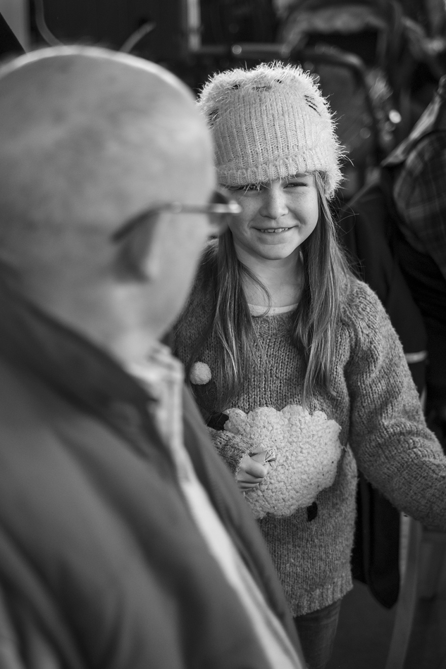 Girl in fluffy hat, smiling at he grandfather, folk and sea shanty songs, The Boathouse in the Marina, Littlehampton West Sussex UK black and white portrait documentary culture folk music ©P. Maton 2018 eyeteeth.net