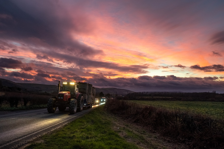 colourful sunset with tractor and headlights illuminating country road with south downs in background, rural west sussex landscape at dusk West Road, Newtimber ©P. Maton 2019 eyeteeth.net