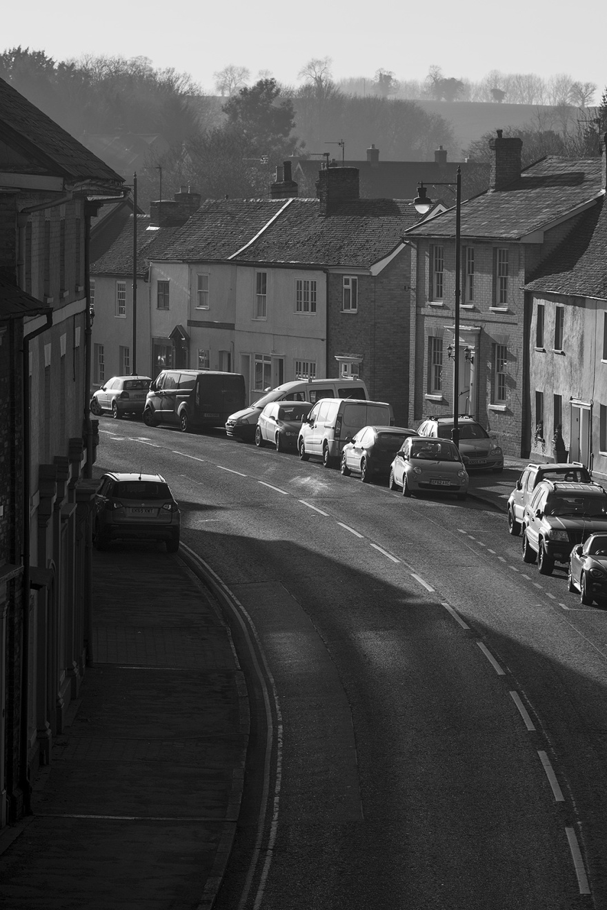 View of street scene with parked cars and trees on distant hill in background, Ballingdon Street Sudbury Suffolk UK black and white rural urban landscape portrait ©P. Maton 2019 eyeteeth.net
