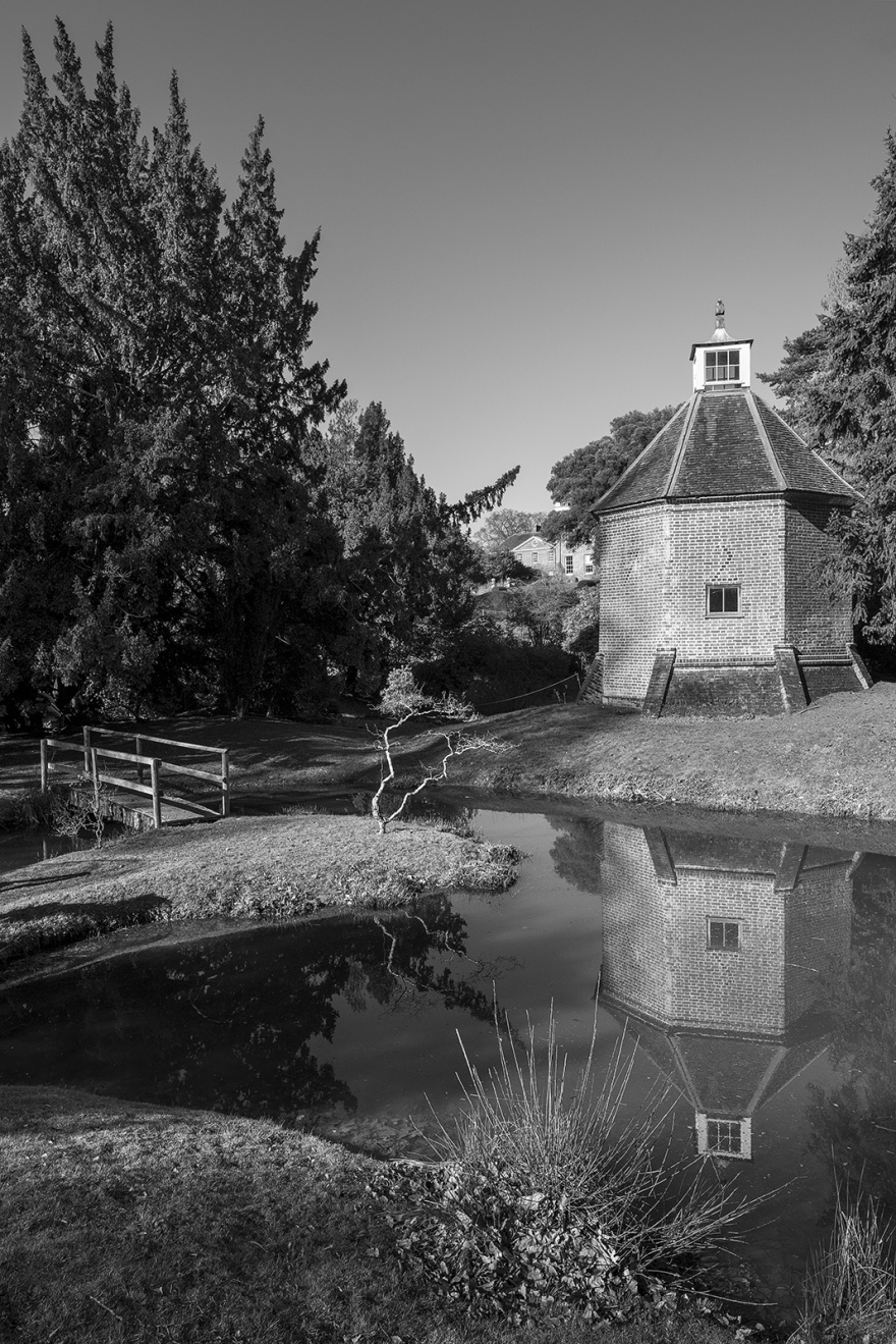 Brick dove cote dated 1720 by ornamental pond with wooden bridge and yew trees and Hedingham Castle manor house in background, Essex UK Abstract composition, sunlight through window casting shadows from chairs, Castle Hedingham Essex UK black and white landscape portrait ©P. Maton 2019 eyeteeth.net