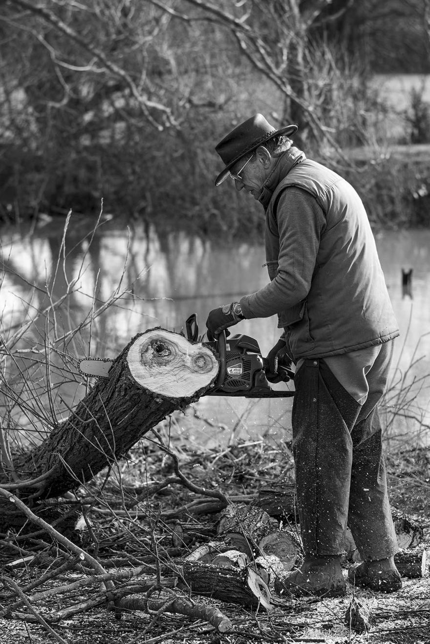 man in hat sawing Willow with a chainsaw, side profile black and white rural environmental portrait Gabriel's Fisheries Kent UK ©P. Maton 2019 eyeteeth.net