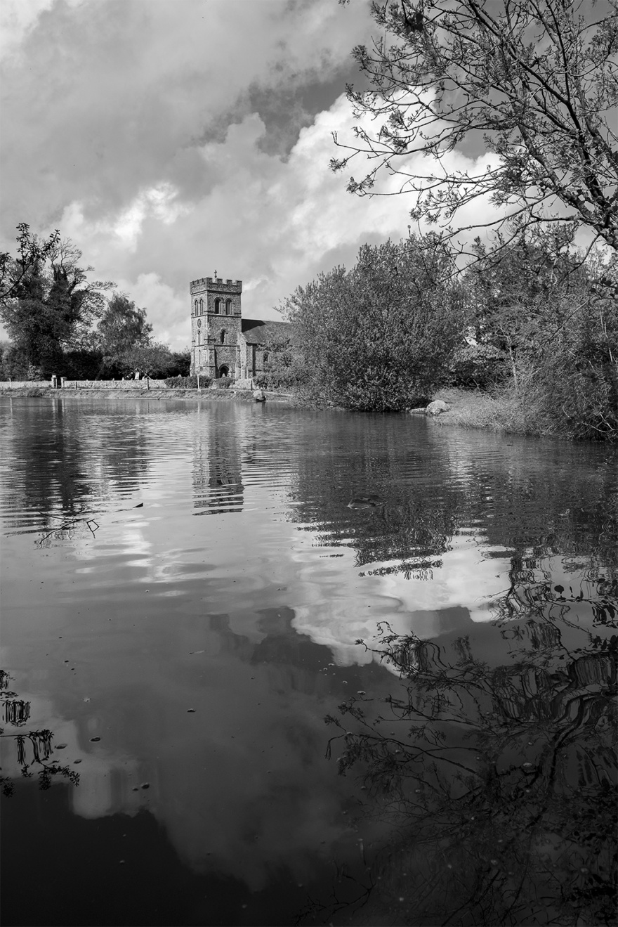 View across pond to Rain Laurence church in Stanmer village East Sussex with clouds in sky UK black and white rural landscape portrait ©P. Maton 2019 eyeteeth.net