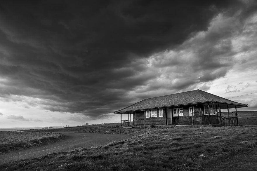 Golf hut on hill with dramatic clouds overhead black and white landscape photograph Rottingdean East Sussex UK ©P. Maton 2019 eyeteeth.net