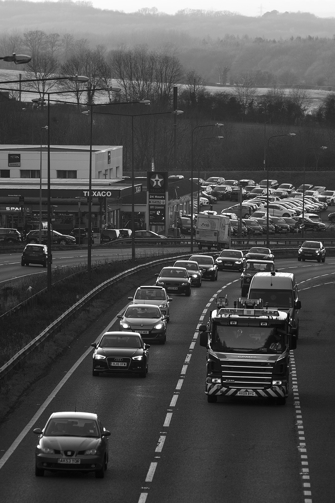 Cars and trucks on dual carriageway with Texaco garage filling station and parked cars in background, rural urban landscape portrait black and white photograph Pyecombe West Sussex UK ©P. Maton 2019 eyeteeth.net