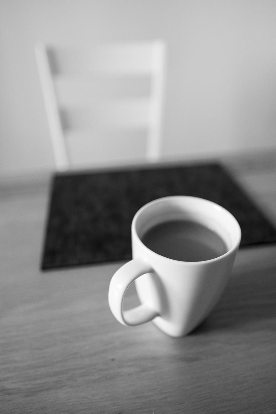 White mug of tea on table with place mat and ladder back chair in background bokeh, black and white lifestyle interior photograph ©P. Maton 2019 eyeteeth.net