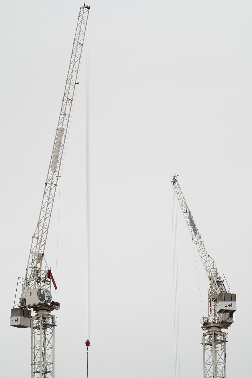 Two tower cranes against a pale grey sky, colour portrait composition industrial machinery grand parade Brighton UK ©P. Maton 2019 eyeteeth.net