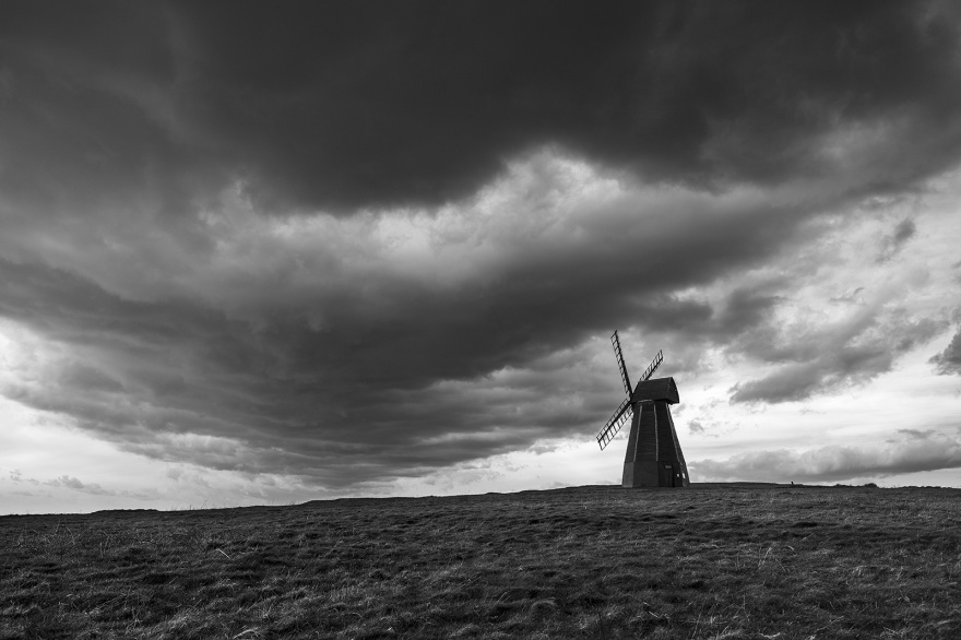 Windmill on hill with dramatic clouds overhead black and white landscape photograph Rottingdean East Sussex UK ©P. Maton 2019 eyeteeth.net