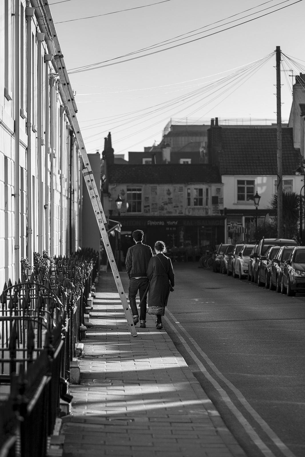 Young couple with linked arms walking away beside ladder down victorian town street, Kensington Place Brighton UK black and white documentary street photography portrait ©P. Maton 2019 eyeteeth.net