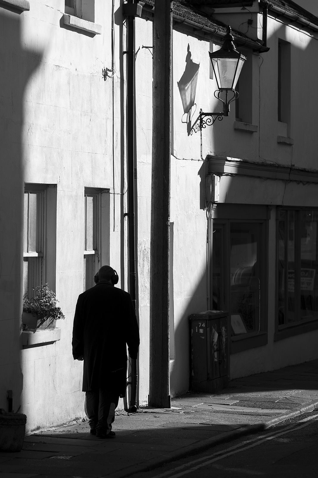 Silhouetted man with headphones walking away into sunlit street with victorian lamp on wall, Queen's Gardens Brighton UK black and white documentary street photography portrait ©P. Maton 2019 eyeteeth.net