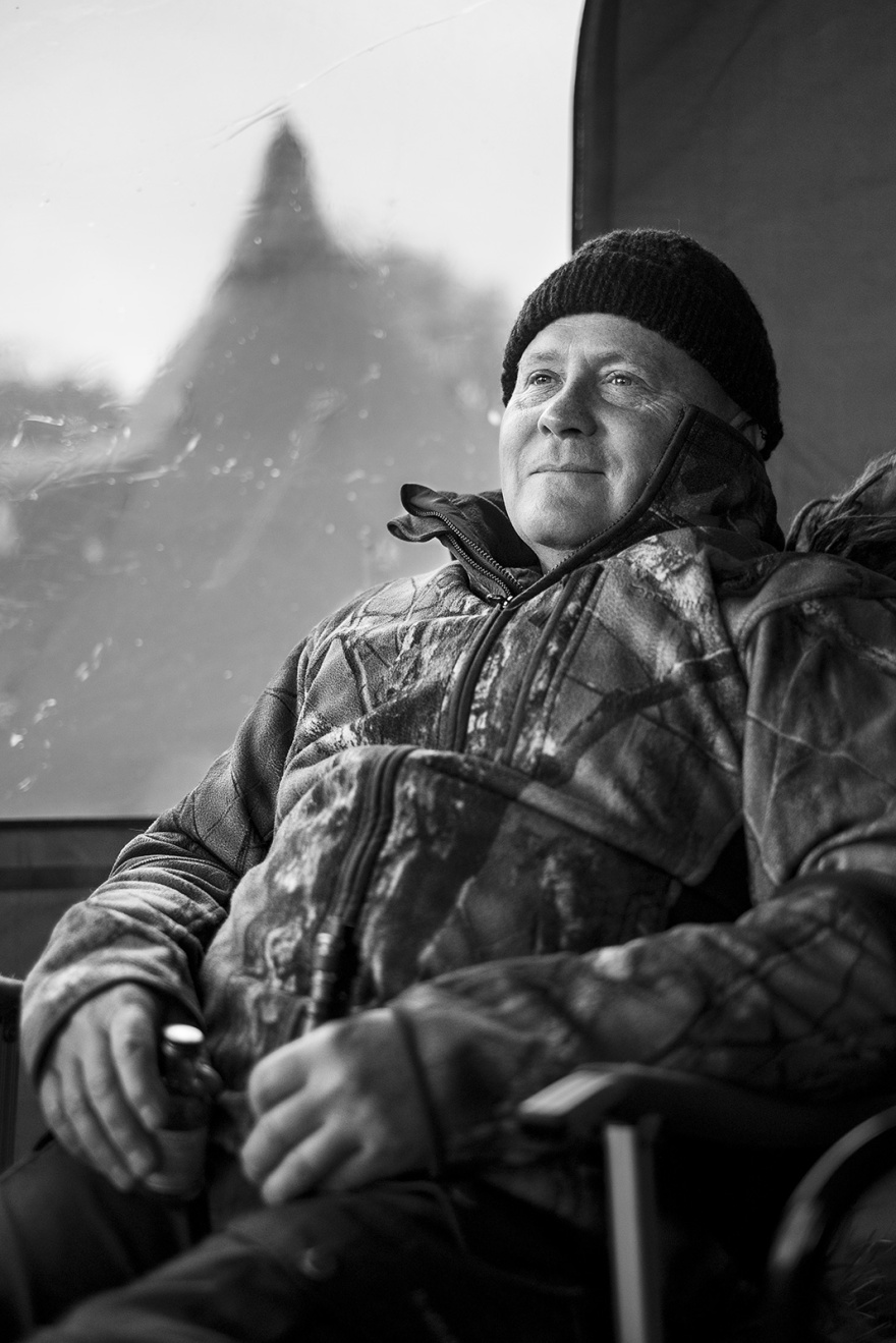 Portrait of a man in hunting clothing and wooly hat with bottle in hand and tent in background, black and white portrait ©P. Maton 2019 eyeteeth.net
