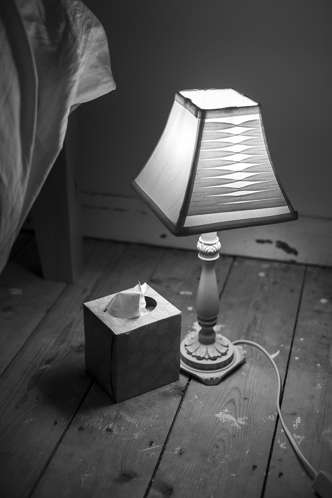 Bedside table lamp on rough wooden floor next to box of tissues, black and white interior documentary photograph portrait © P. Maton 2019 eyeteeth.net
