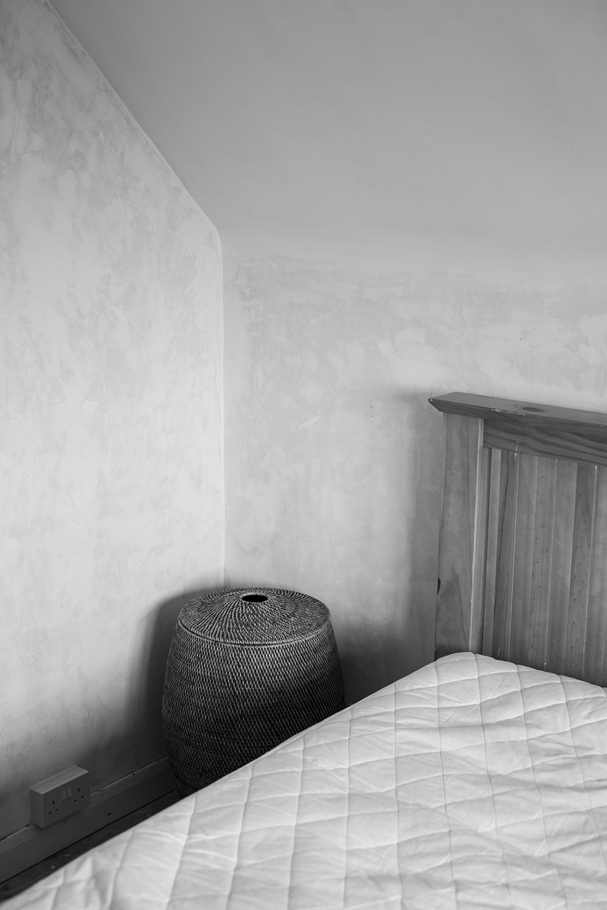 Woven laundry basket in corner of room with distressed wall next to bed with bare mattress black and white interior documentary photograph portrait © P. Maton 2019 eyeteeth.net