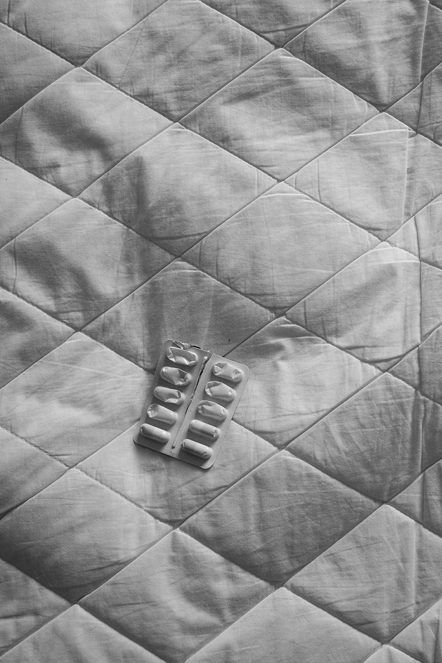 Half used blister pack of medication capsules on bed with quilted mattress protector black and white documentary photograph portrait © P. Maton 2019 eyeteeth.net