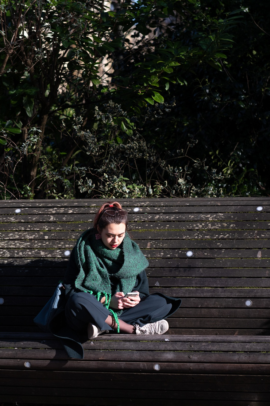Fashionable stylish young woman sitting with crossed legs on bench studying mobile phone, New Road Brighton UK colour documentary street photography portrait ©P. Maton 2019 eyeteeth.net